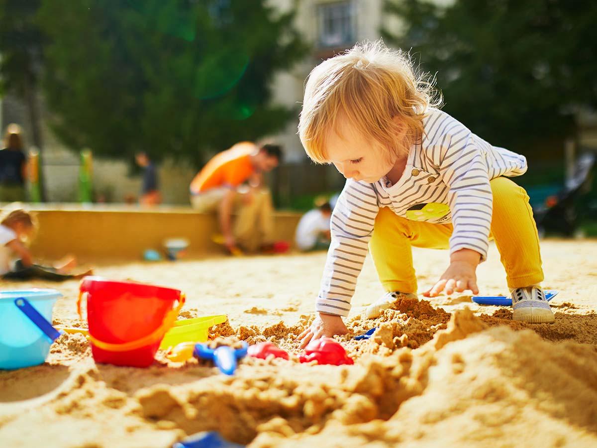 Kleines Mädchen spielt in Sandkasten von Kinder-Spielplatz