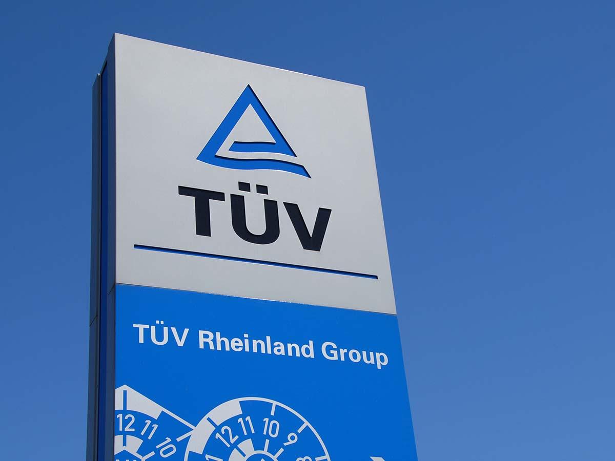 Schild der TÜV Rheinland Group vor blauem Himmel