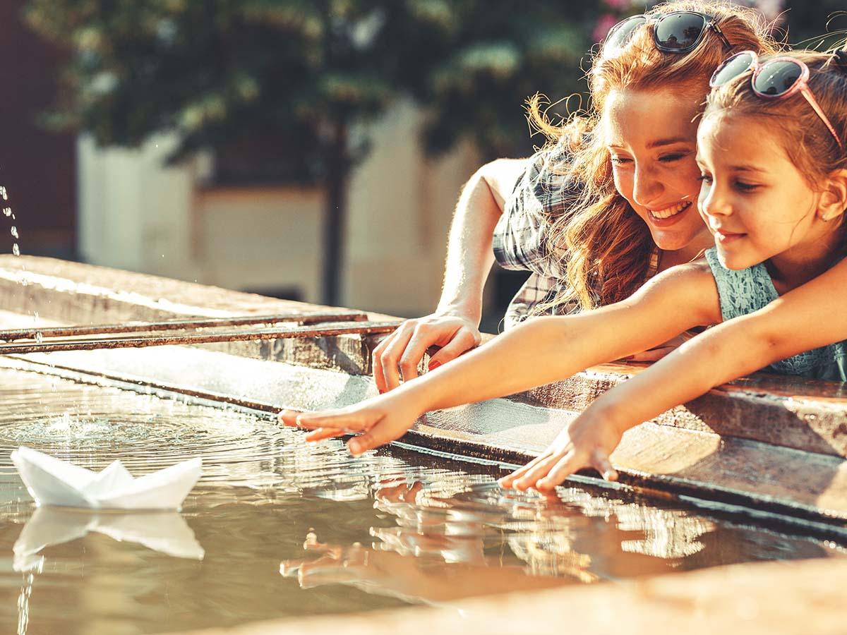 Mutter spielt mit Tochter auf Wasser-Spielplatz