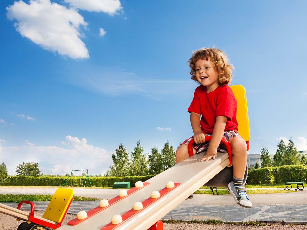 Kind hat Spaß auf Wippe auf Kinder-Spielplatz