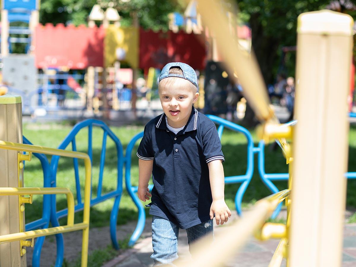 Kind mit Down-Syndrom spielt auf inklusivem Kinder-Spielplatz