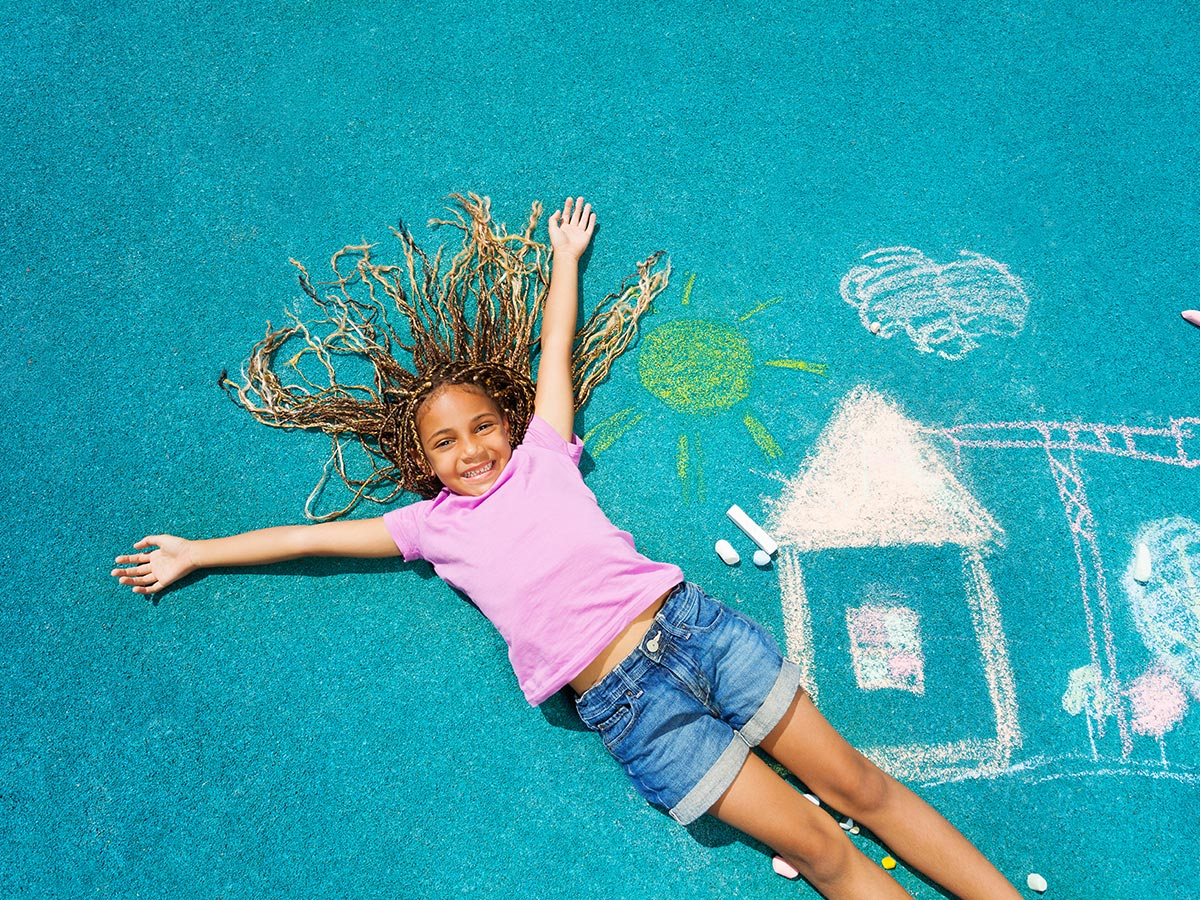Mädchen liegt auf buntem Fallschutzboden auf Kinder-Spielplatz
