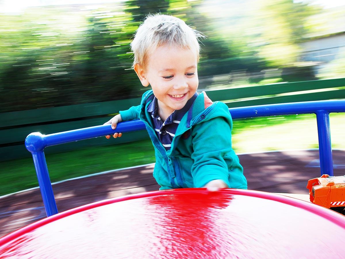 Junge spielt in Karussel auf Kinder-Spielplatz