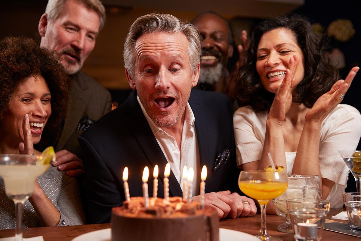 Mann pustet Kerzen zum 50. Geburtstag aus
