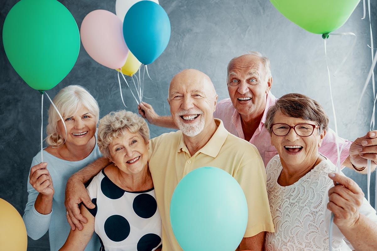 Senioren feiern zusammen Geburtstag mit Ballons