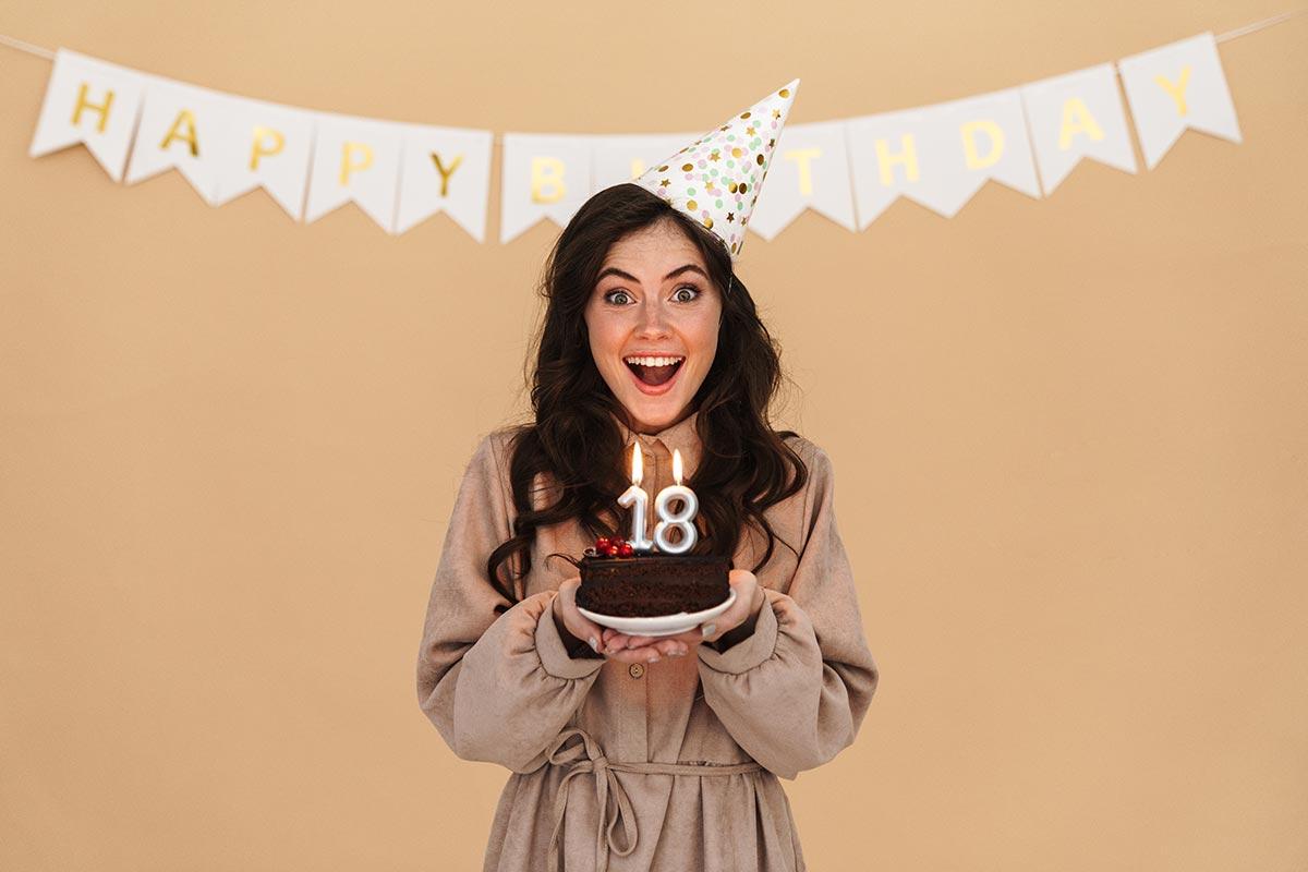 Junge freut sich über Torte und Geburtstagsnachricht zum 18.