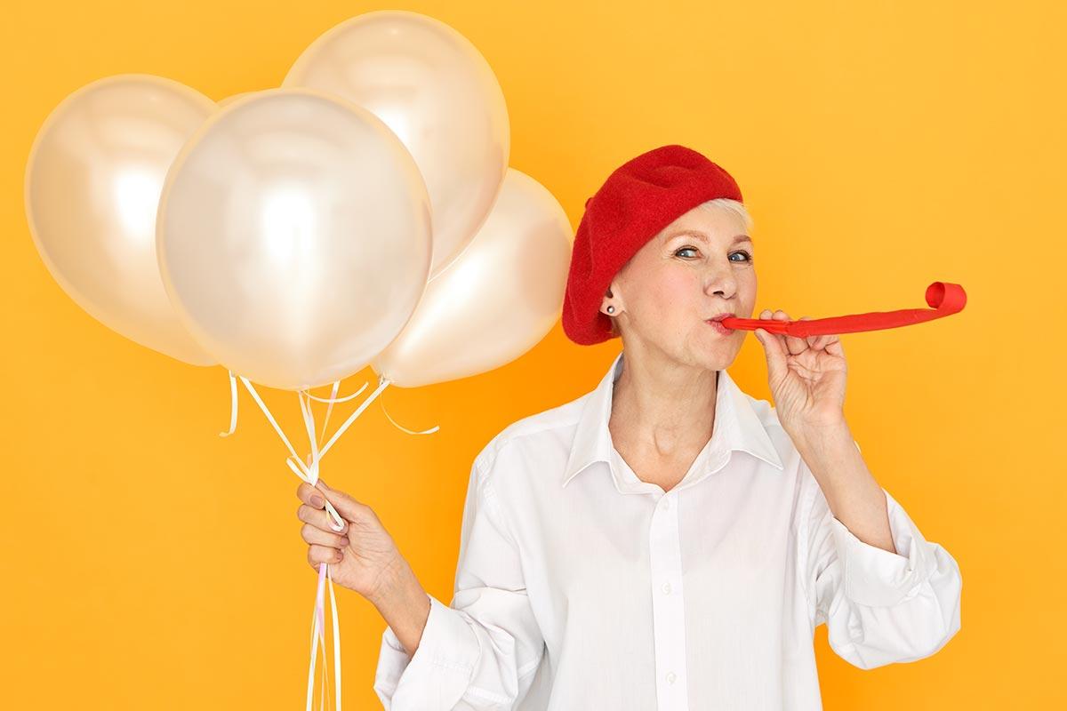 Frau mit Luftballons freut sich an Geburtstag