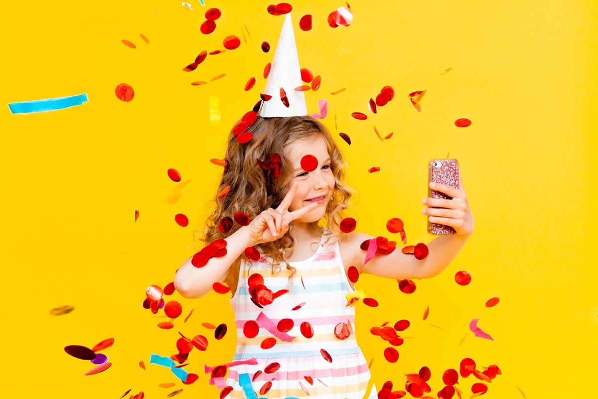 Mädchen macht Selfie mit Konfetti und Partyhut zum Jubeltag