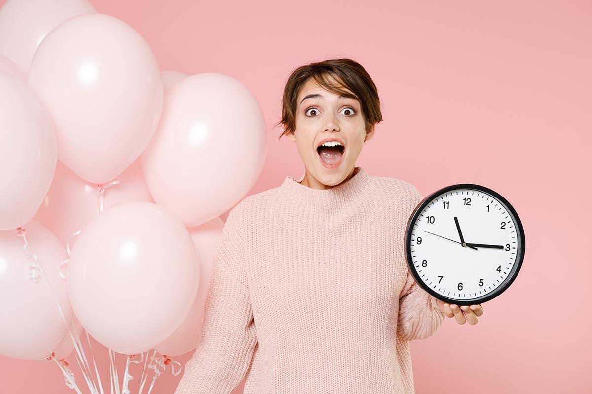 Junge Frau hält Uhr und Ballons zu nachträgliche Geburtstagswünschen