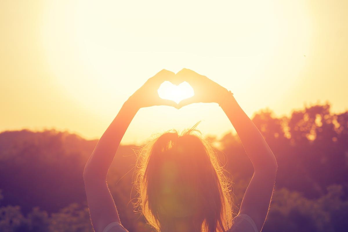 Junge Frau formt Herz mit Händen in den Sonnenuntergang