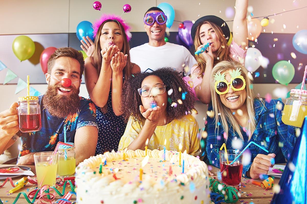 Freunde feiern Geburtstag mit Torte, Konfetti und schönen Glückwünschen zum Geburtstag