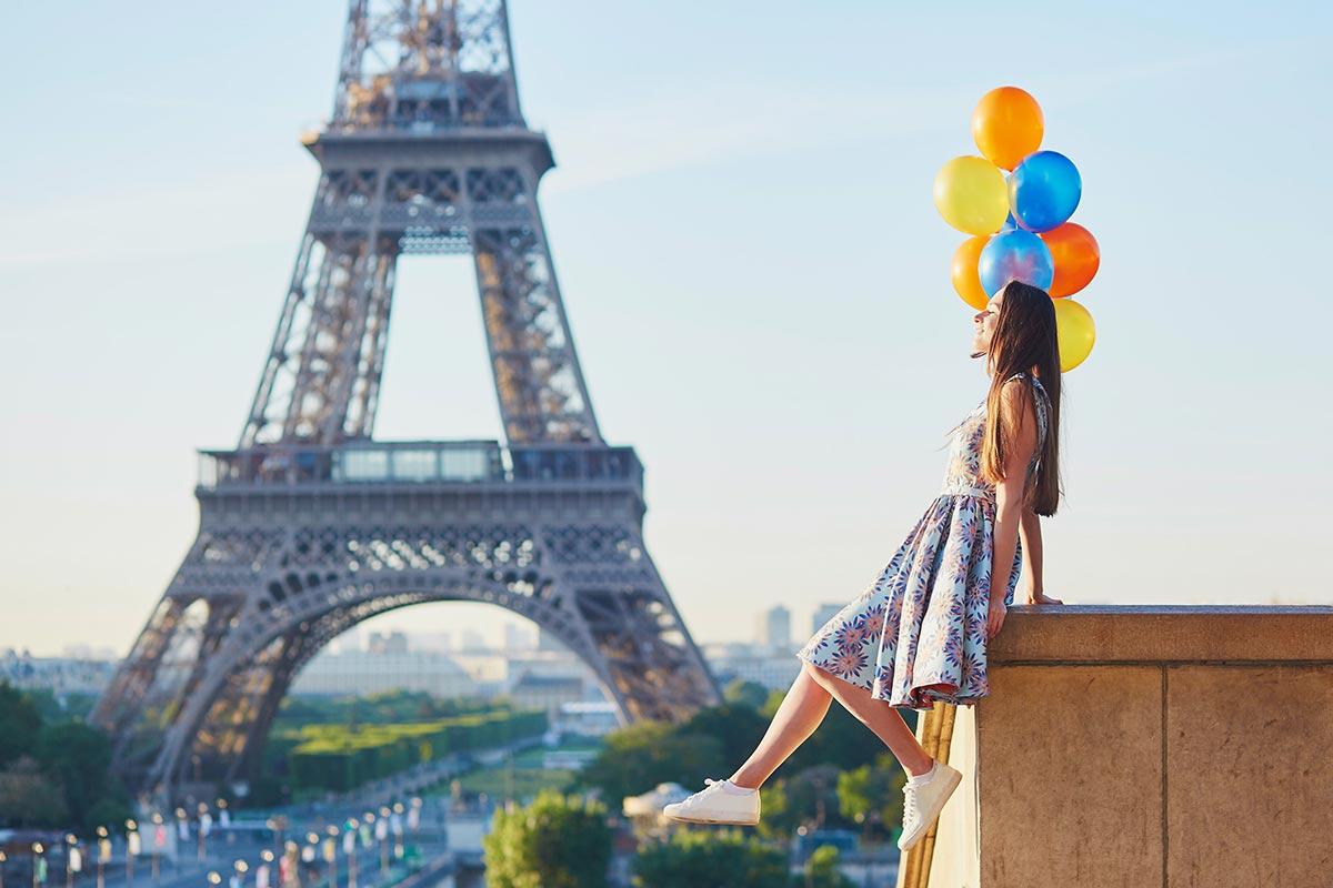 Junge Frau mit Luftballons zum Geburtstag vor Eiffelturm