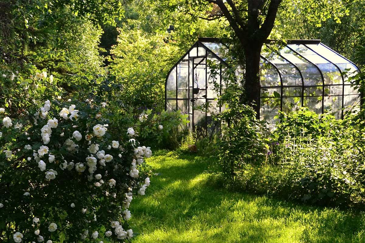 Gewächshaus im blühenden Garten