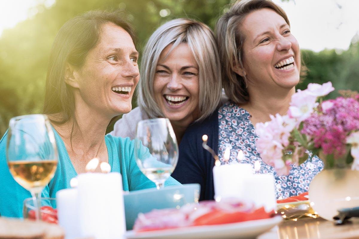 Frauen lachen auf Gartenparty über dumme & lustige Sprüche