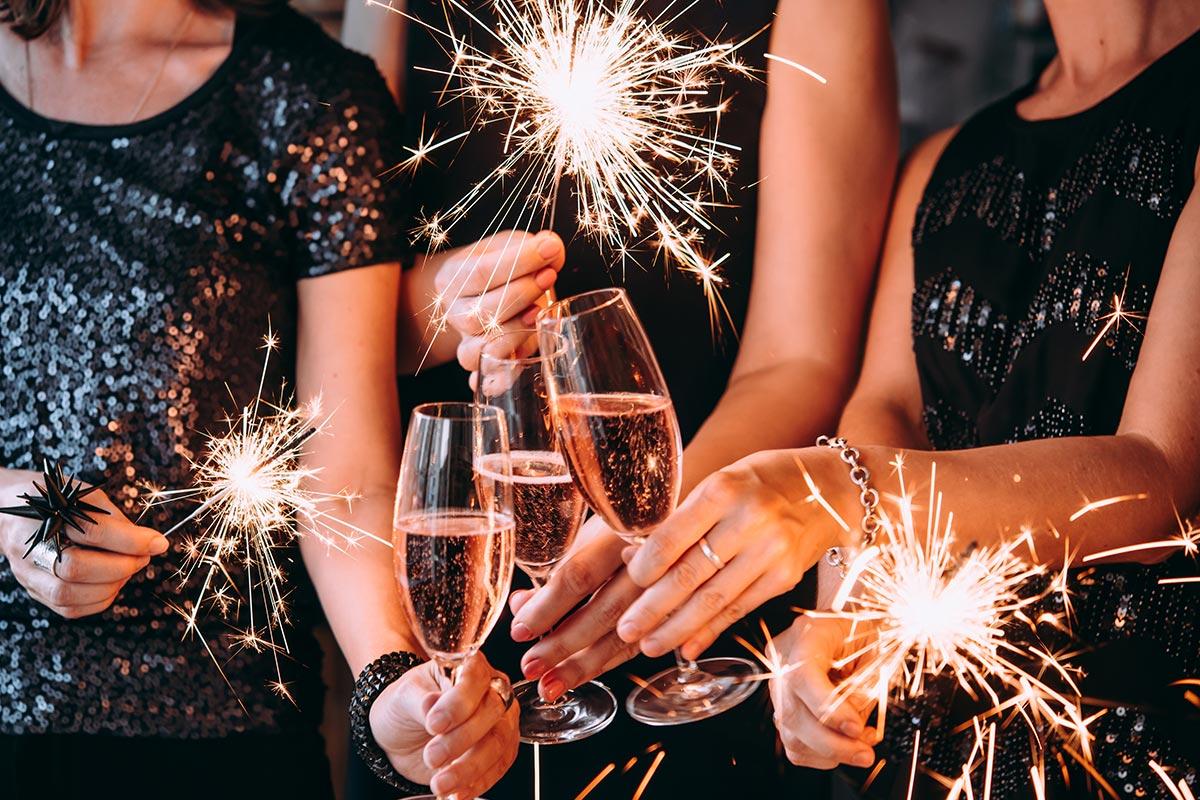 Frauen feiern mit lustigen Sprüchen,Sekt und Wunderkerzen Silvester