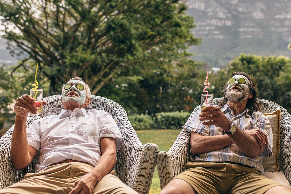 Zwei ältere Männer entspannen mit Cocktail und Gesichtsmaske in Natur