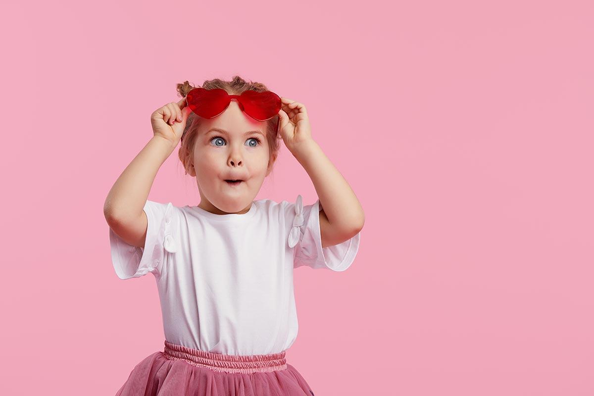 Kleines lustiges Mädchen vor rosa Hintergrund