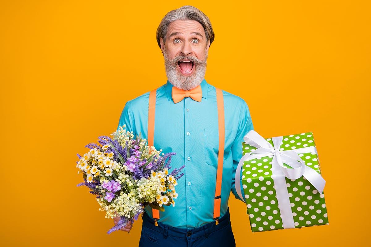 Cooler ältere Mann mit Geschenk und Blumenstrauß