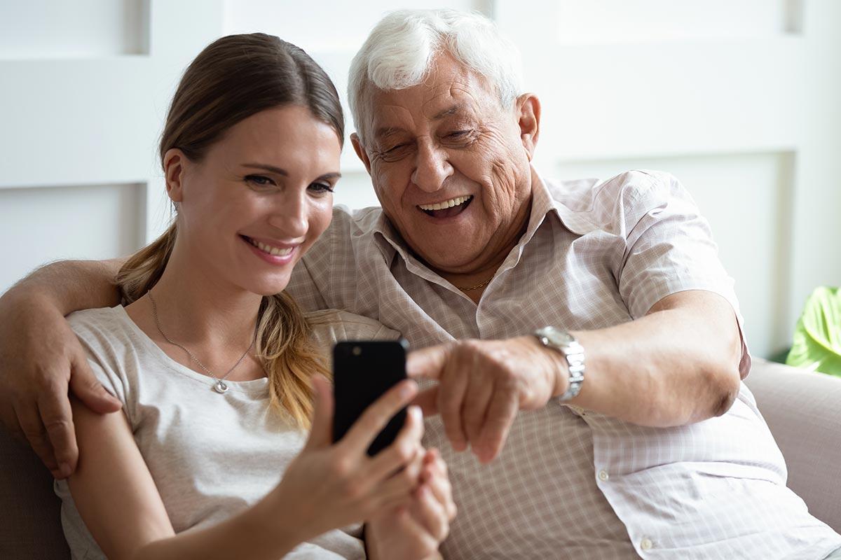 Opa und Enkelin lachen über witzige WhatsApp-Sprüche