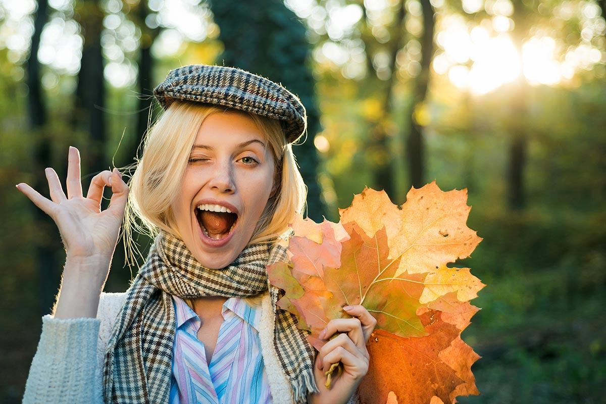 Junge Frau in Herbstwald mit farbigen Blättern