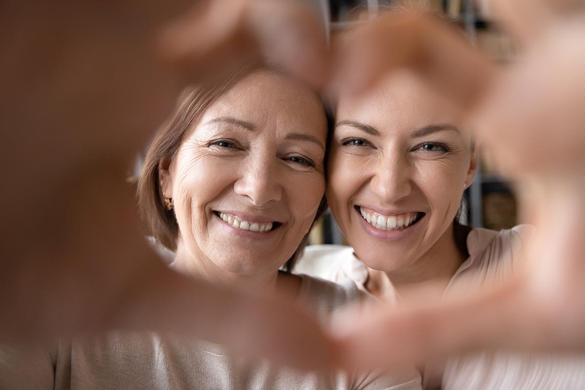 Mutter und Tocher formen Herz mit Händen