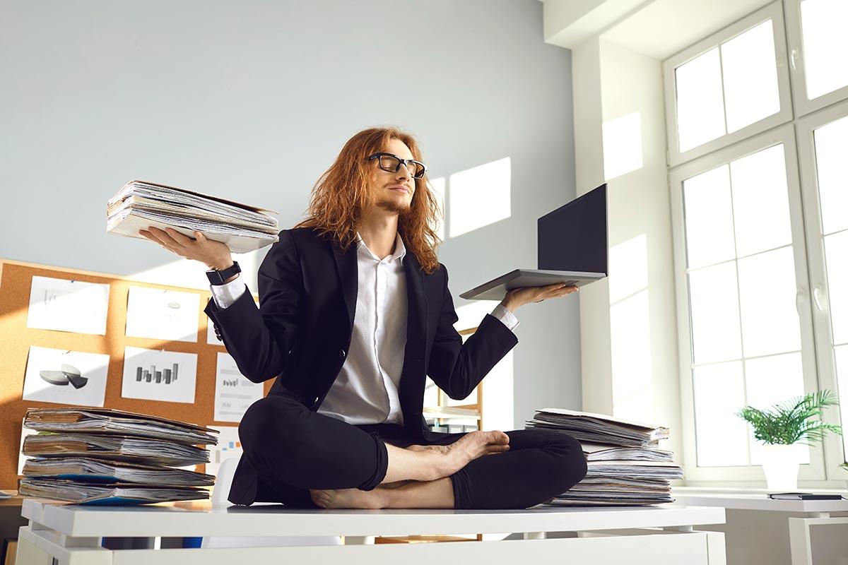 Angestellter in Büro balanciert Laptop und Akten in Yoga Pose