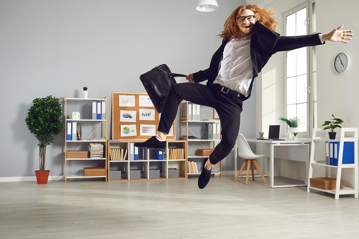 Geschäftsmann freut sich über lustige Sprüche zum Freitag und springt