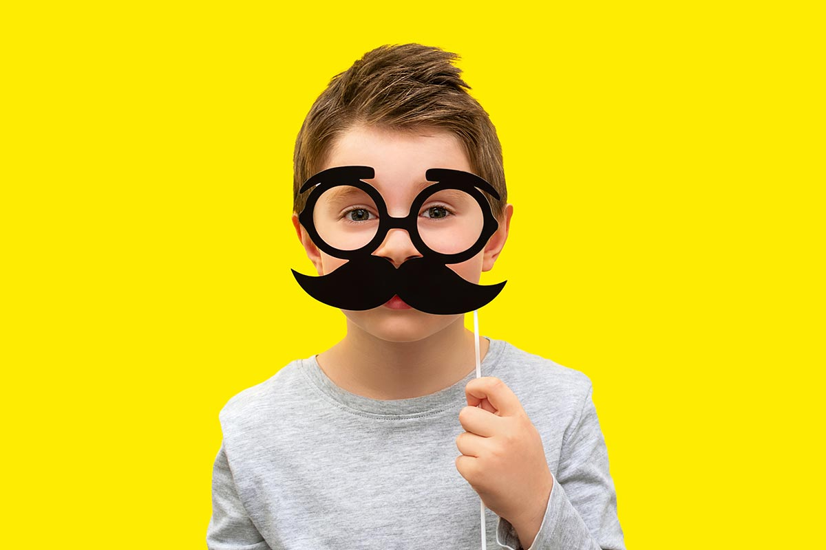 Junge mit lustigem Schnurrbart und Brille vor gelbem Hintergrund