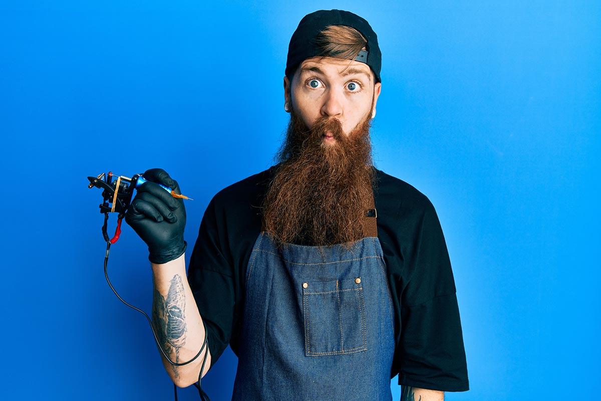 Junger Tätowierer mit langem Bart vor blauem Hintergrund