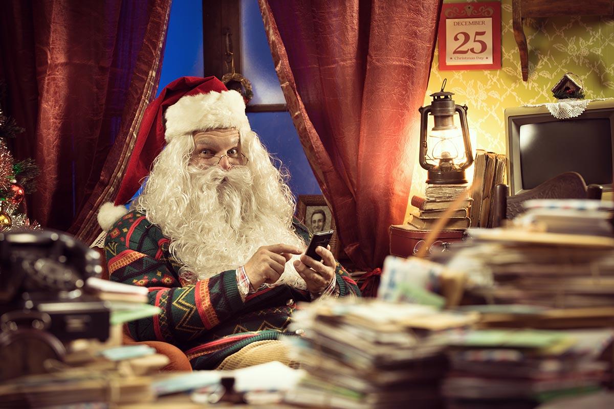 Weihnachtsmann schreibt lustige Weihnachtsgrüße per WhatsApp an Schreibtisch
