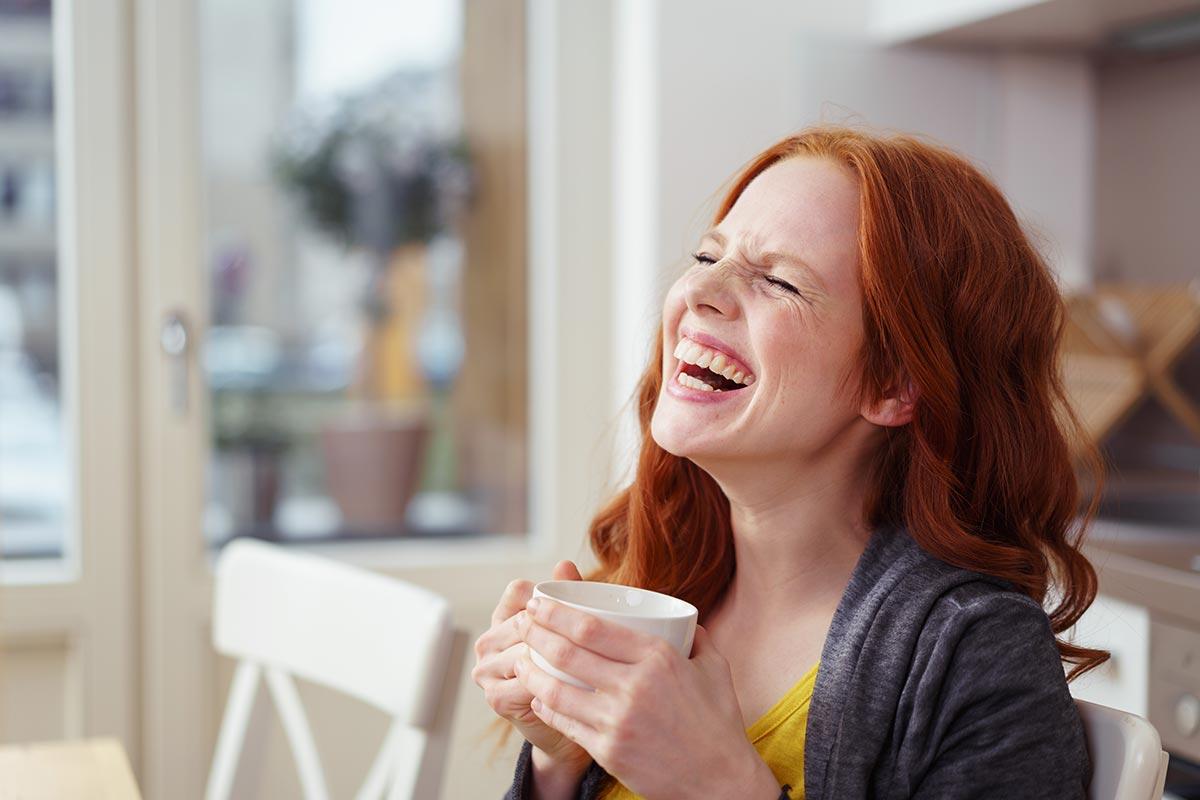 Junge Frau lacht über lustige Guten-Morgen-Sprüche am Morgen