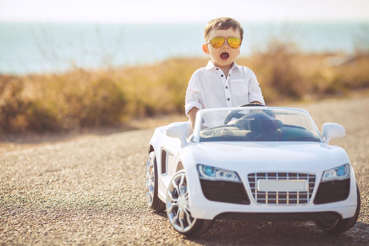Kleiner cooler Junge sitzt in coolem Kinder-Auto