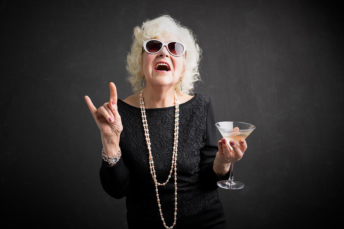 Coole Oma mit Cocktail lacht über lustige Rentner-Sprüche
