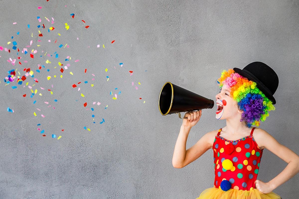 Kind als Clown verkleidet verteilt Konfetti mit Sprachrohr