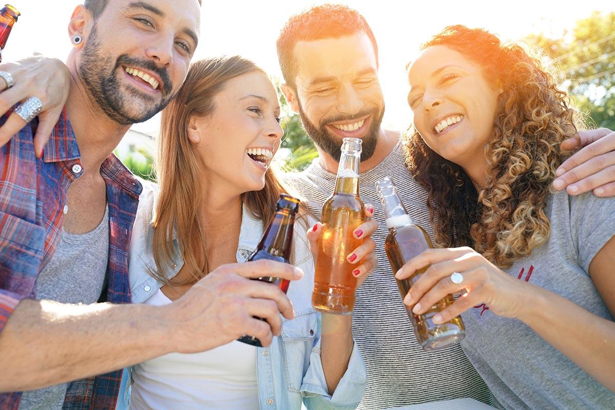 Freunde trinken Bier und lachen über lustige Trink-Sprüche