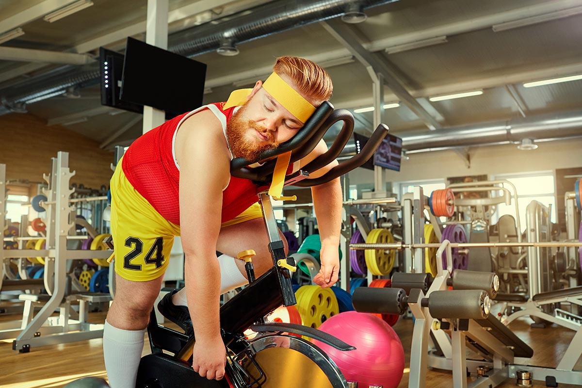 Unsportlicher Mann schläft auf Fahrrad in Fitnessstudio