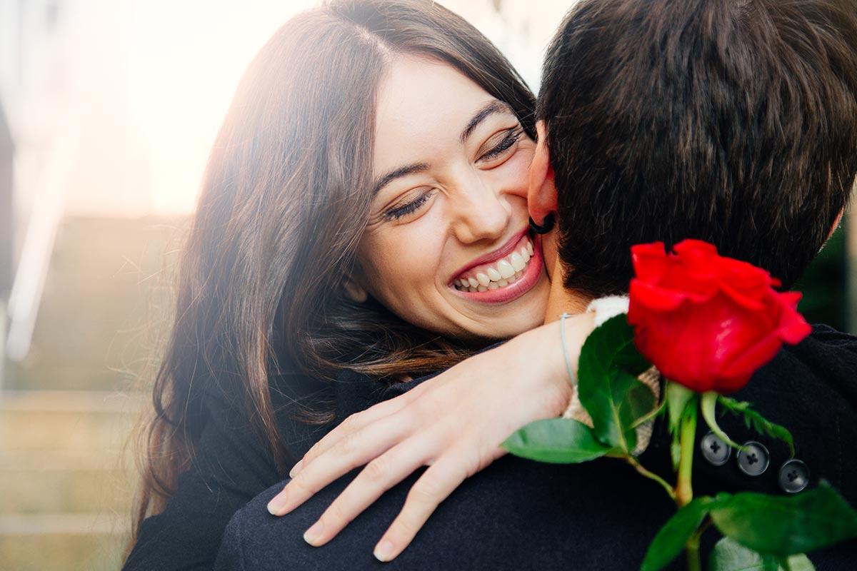 Frau mit Mann freut sich über Rose und witzige Valentinstagssprüche