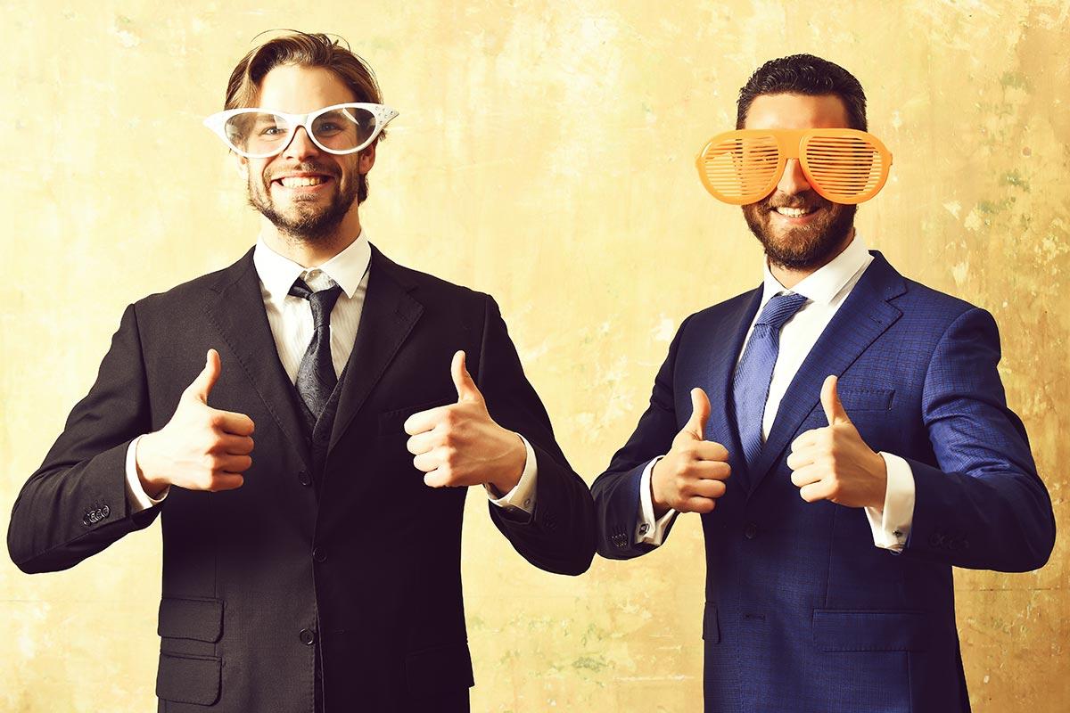 Zwei Geschäftsleute albern herum mit lustigen Brillen und witzigen Sprüchen