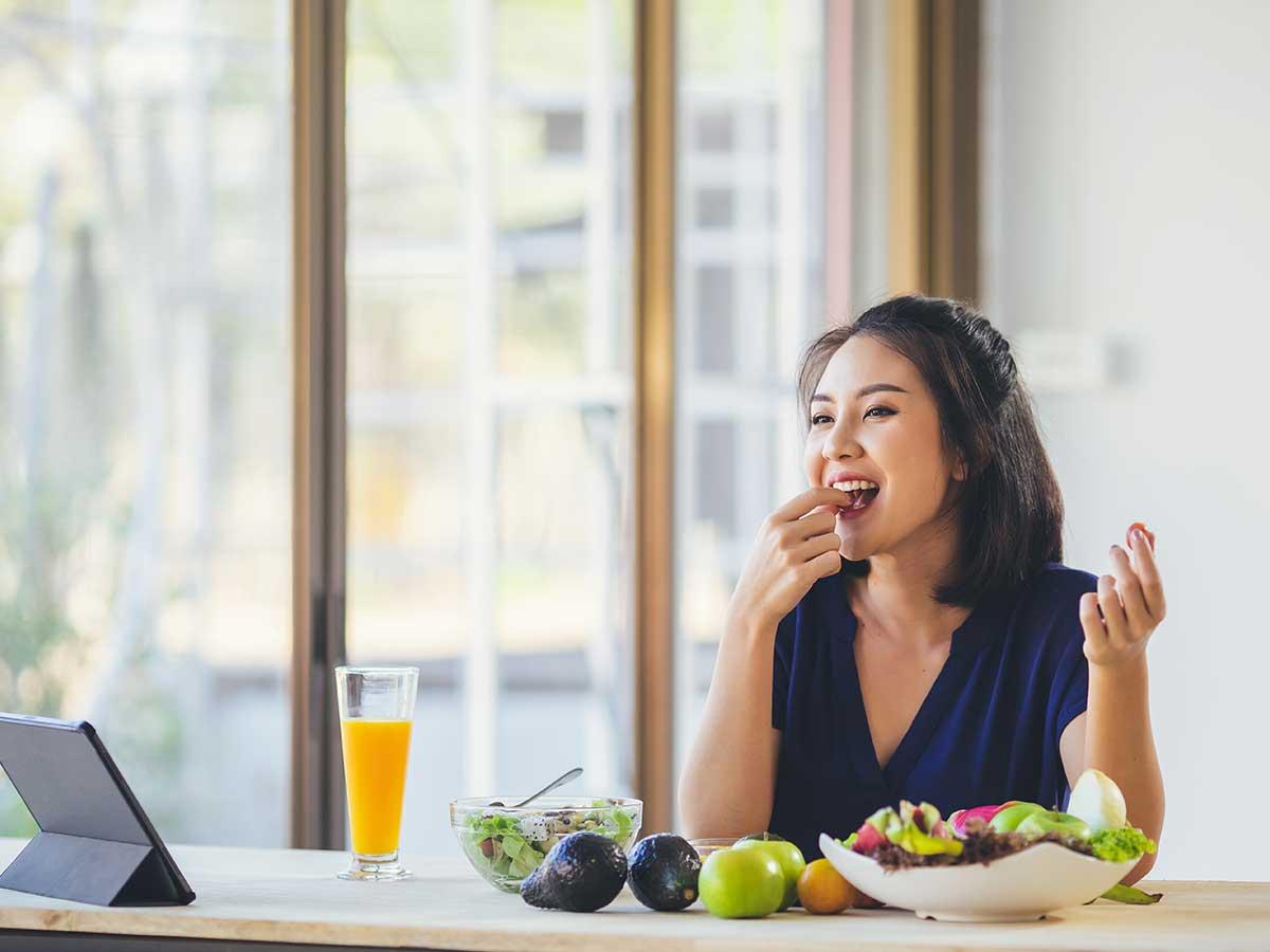 Frau isst Avocado und Gesundes
