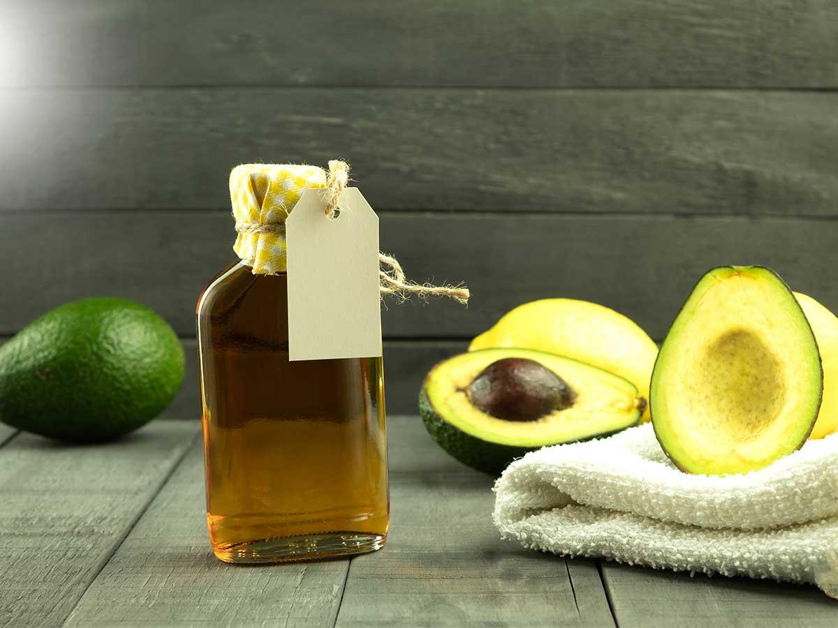 Avocado-Hälften und Ölflasche