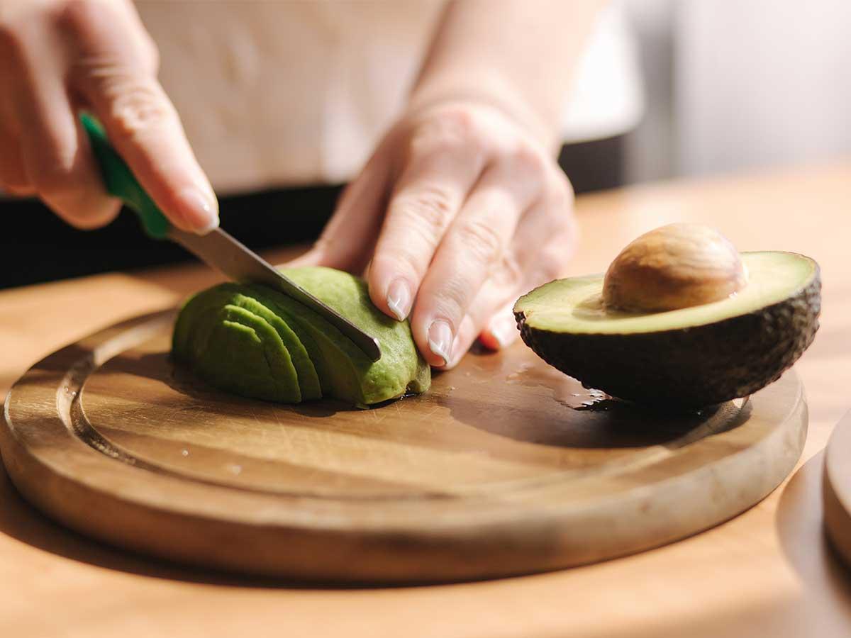 Frau schneidet Avocado auf Holzbrett